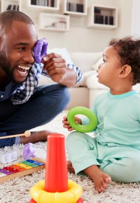A man and young child play with toys