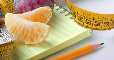 fruit, paper and pencil, and measuring tape